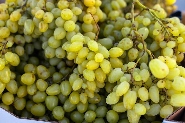 Vers fruit brunch groene druiven in papieren dozen op de lokale fruitmarkt in de stad