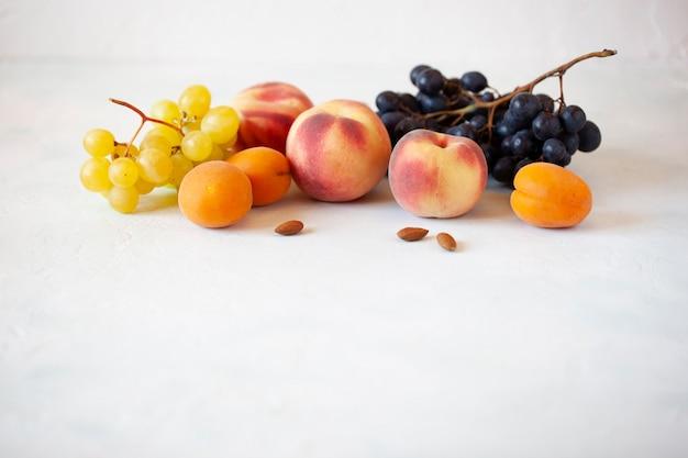 Vers fruit en amandelen op de witte achtergrond, gezondheidsvoedselconcept, witte achtergrond, zijaanzicht, kopieerruimte, banner