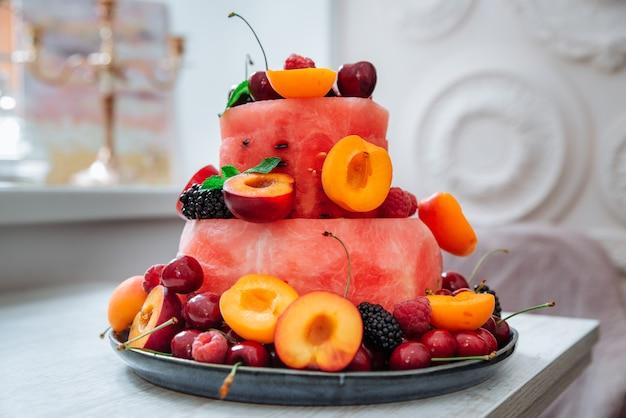 Vers fruit en bessensalade in de vorm van een cake versierd met muntblaadjes zomerdessertconcept