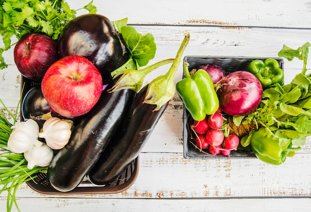 Vers fruit; en groenten in plastic mand over houten tafel