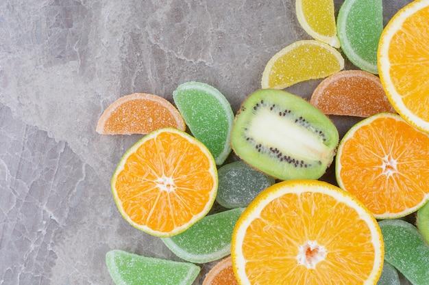 Vers fruit met zoete marmelades op marmeren achtergrond.
