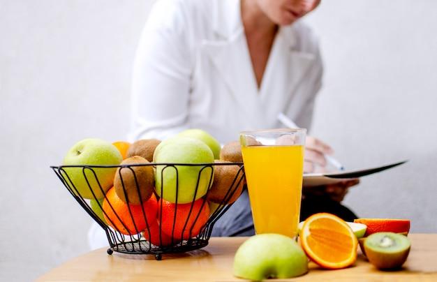Vers fruit op het bureau en vrouwelijke voedingsdeskundige schrijven recept voor gezond eten tijdens de uitbraak van coronavirus