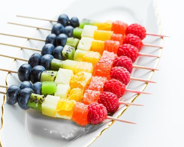 Vers fruit op spiesjes in plaat op tafel