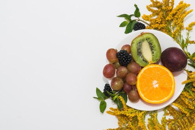 Vers fruit op witte plaat met gele bloemen tegen witte achtergrond