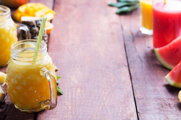 Vers fruit smoothie en stukjes fruit op een donkere houten rustieke tafel