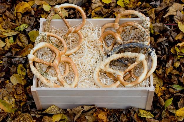Vers geassorteerde pretzels in een houten doos op achtergrond van de herfst geel gebladerte.