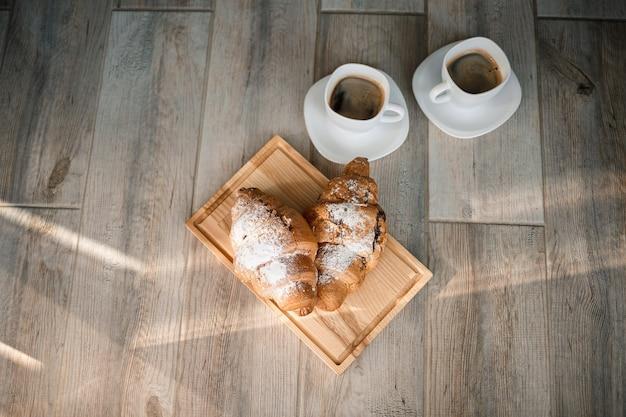 Vers gebak croissants met chocolade op een houten bord en twee kopjes zwarte koffie. romantisch ontbijt