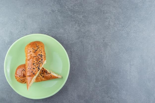 Vers gebak met sesamzaadjes op groene plaat.