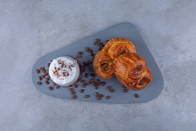 Vers gebakje met glas koffie en koffiebonen op houten raad.