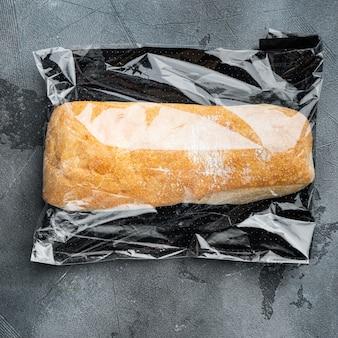 Vers gebakken ambachtelijk volkoren ciabattabrood in een marktzak, op grijze achtergrond, bovenaanzicht plat lag