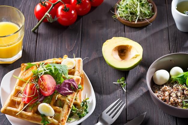 Vers gebakken belgische wafels met rucola, tomaten en avocado op een bord