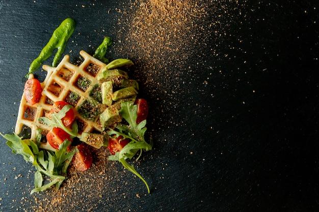 Vers gebakken belgische wafels met rucola, tomaten en avocado op zwart een plaat. hartige wafels. ontbijt concept