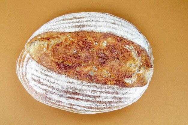 Vers gebakken biologisch zuurdesembrood geïsoleerd op bruin of koffie achtergrond. een heerlijk vers boekweitbrood. ecologisch voedsel. bovenaanzicht, plat gelegd.
