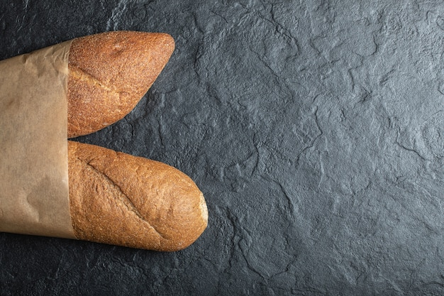 Vers gebakken brits stokbroodbrood op zwarte achtergrond.