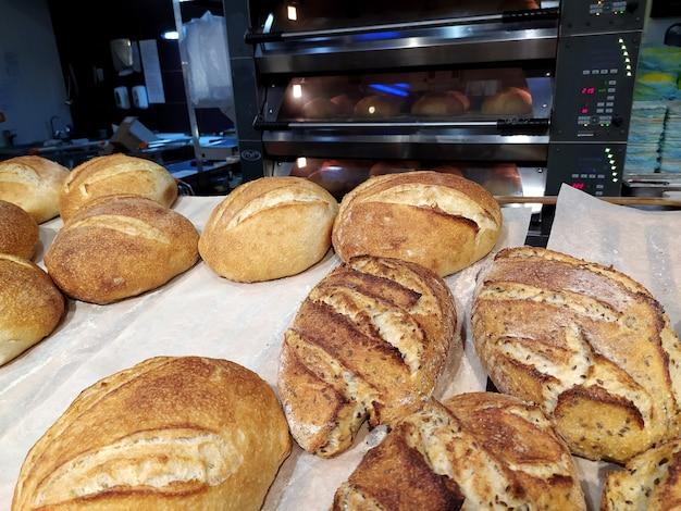 Vers gebakken broden liggen op een dienblad in een bakkerij, op de achtergrond is er een hete oven.