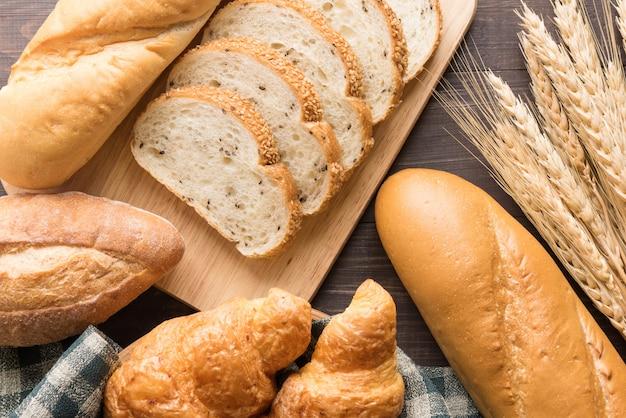 Vers gebakken brood en tarwe op houten achtergrond