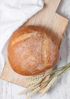 Vers gebakken brood met keukenhanddoek en tarwe op witte houten bord
