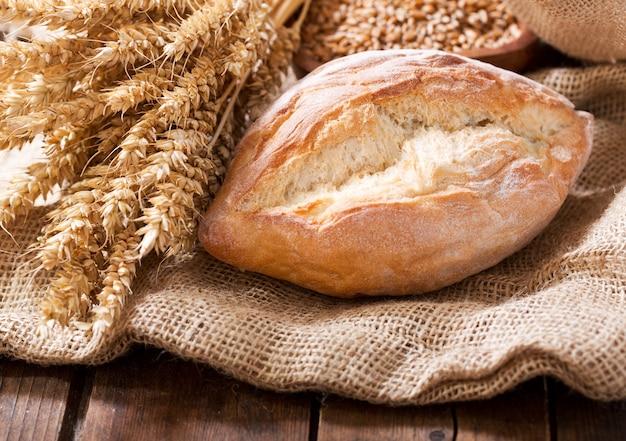 Vers gebakken brood met tarwe oren op houten tafel