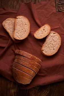 Vers gebakken brood op donkere houten keukentafel.