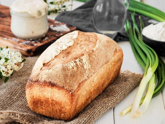 Vers gebakken brood op jute, zuurdesem en bloem met een kruik water op een witte houten tafel