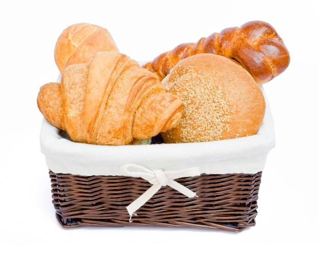 Vers gebakken broodjes in een mand op wit