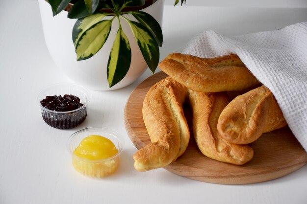 Vers gebakken broodjes onder witte theedoek op houten snijplank, jam en honing geserveerd voor het ontbijt op witte tafel