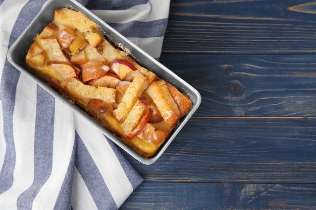 Vers gebakken broodpudding in braadpanschotel op houten lijst