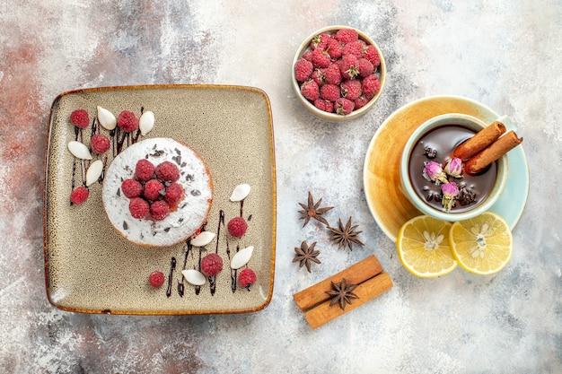 Vers gebakken cake met frambozen een kopje zwarte thee met citroen en kaneel limoen