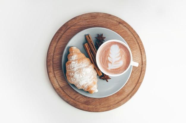 Vers gebakken croissant met koffiekopje en latte art, kaneel