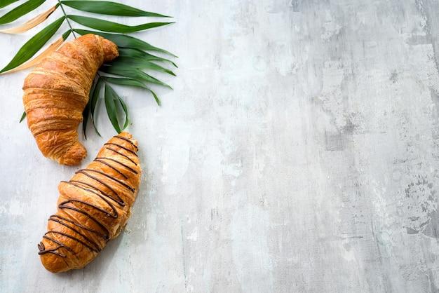 Vers gebakken croissant versierd met chocoladesaus en palm verlaat