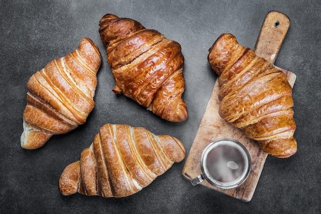 Vers gebakken croissants en een kopje koffie op tafel. het uitzicht vanaf de top