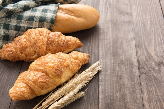 Vers gebakken croissants en stokbrood op houten tafel