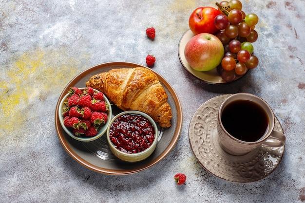 Vers gebakken croissants met frambozenjam en frambozenfruit.