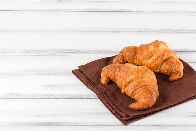 Vers gebakken croissants op bruin servet op witte oude houten achtergrond. vers gebak voor het ontbijt. heerlijk dessert. close-up fotografie. selectieve aandacht. horizontale banner.