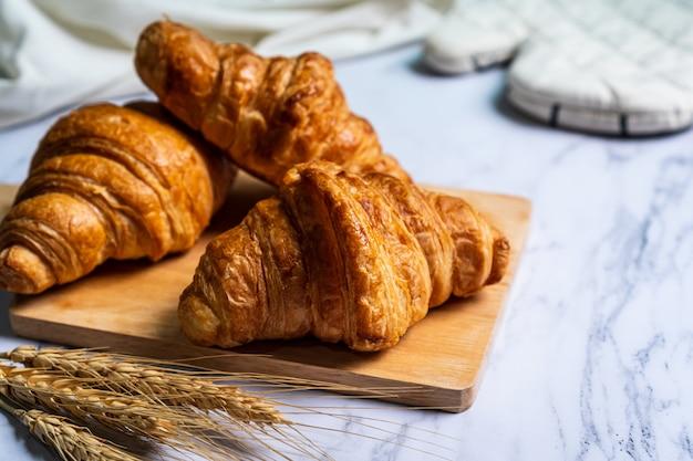 Vers gebakken croissants op houten snijplank.