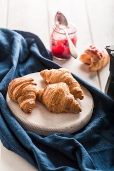 Vers gebakken franse croissants met een potje jam op een licht houten tafel met een blauwe servet.