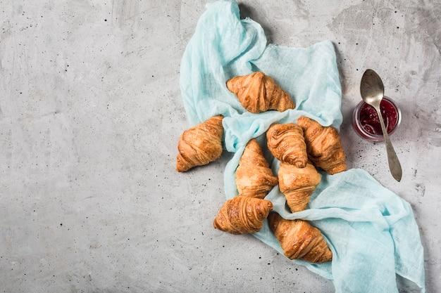 Vers gebakken franse croissants met een potje jam op een lichtgrijze tafel met een turquoise servet.