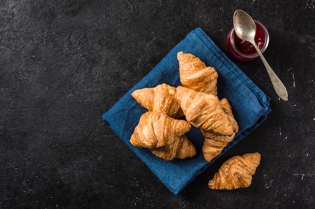 Vers gebakken franse croissants met een potje jam op een zwarte tafel met een donker blauwe servet.