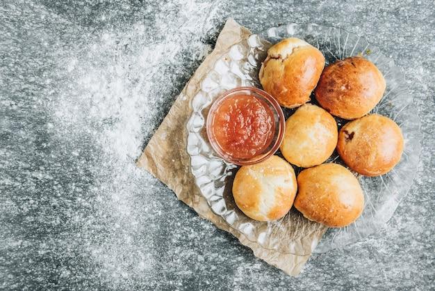 Vers gebakken gistbroodjes gevuld met appeljam op grijze achtergrond met bloem.
