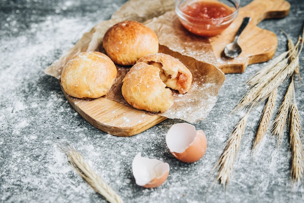 Vers gebakken gistbroodjes gevuld met appeljam op grijze ondergrond met bloem.