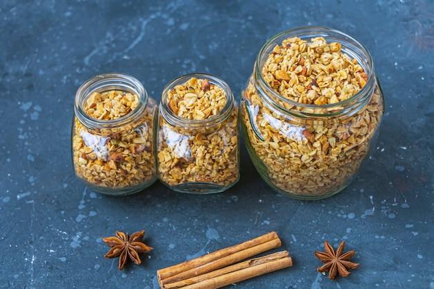 Vers gebakken granola, muesli van havervlokken, verschillende soorten noten, honing, pompoenpitten in glazen pot. thuis koken gezonde vegetarische snack. zelfgemaakt voedselconcept. keto-dieet.