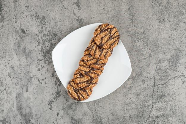Vers gebakken havermoutkoekjes die met zaden op witte plaat worden bestrooid.