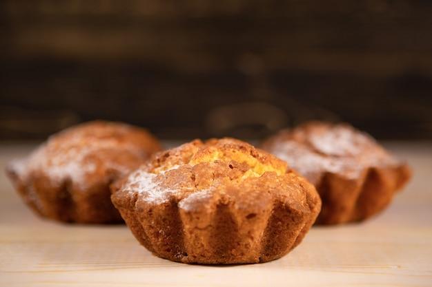 Vers gebakken heerlijke cupcakes in poedersuiker op een houten tafel.