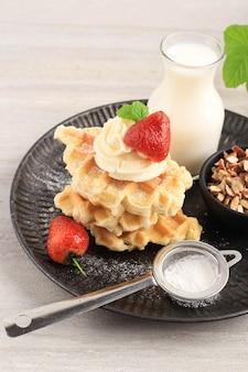 Vers gebakken heerlijke zelfgemaakte croissantwafel met ahornsiroop, gehakte amandel en aardbei. geserveerd op zwarte plaat, bruine achtergrond.