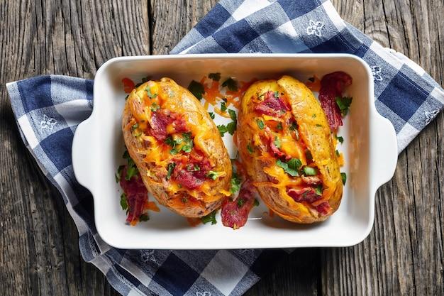 Vers gebakken hete aardappelen geladen met krokant gebakken spek, getrokken kipfilet en gesmolten cheddarkaas in een ovenschaal op een rustieke houten tafel, uitzicht van bovenaf, close-up