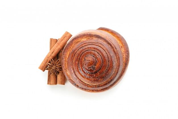 Vers gebakken kaneelbroodje met ingrediënten die op wit worden geïsoleerd