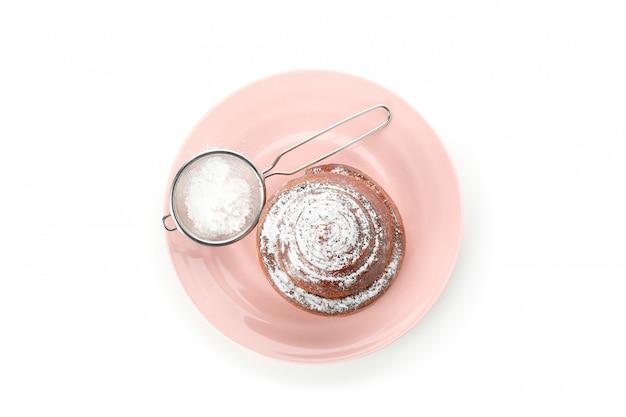 Vers gebakken kaneelbroodje met poeder op plaat die op wit wordt geïsoleerd