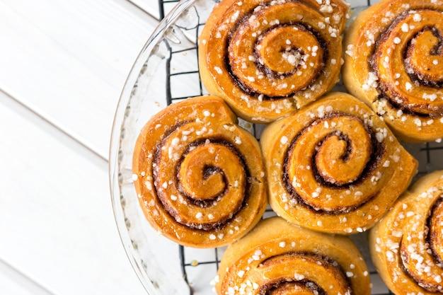 Vers gebakken kaneelbroodjes met kruiden op een houten achtergrond. kanelbule - zweeds dessert. voedsel concept. bovenaanzicht, plat gelegd