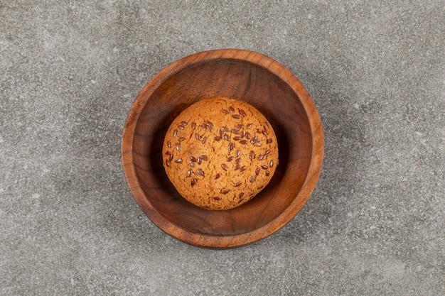 Vers gebakken koekje in houten kom over grijs.