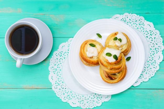 Vers gebakken kwarkbroodjes met room en muntblaadjes en een kopje thee
